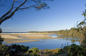 Australian coastal landscape with sandy beaches hemmed by forests and blue water of ocean under blue sky near Mallacoota, Victoria, Australia