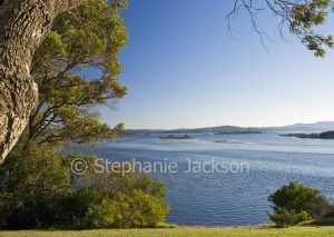 Vast blue waters of Mallacoota inlet, a coastal estuary, hemmed by ranges in Victoria Australia