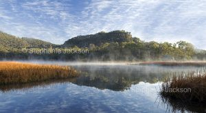 Stunning landscape with dawn mist rising from lake, with hill, forest, and blue sky flecked with clouds reflected in calm water of wetlands at Dunn's swamp in Wollemi National Park in NSW Australia