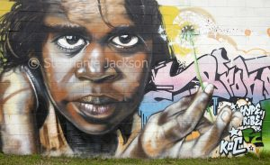 Street art / mural, portrait of aboriginal woman / girl painted on wall of building in Kempsey, NSW Australia