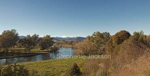 Panoramic view of Murray River in a forested landscape with the snow-capped peaks of the Snowy Mountains in the distance - near Corryong in Victoria, Australia.