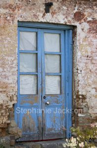 Old blue door with flaking pain in crumbling brick wall of old building in Braidwood NSW Australia