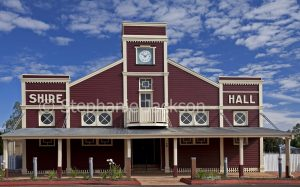 Burgundy red and white old shire hall under blue sky in Surat, outback Queensland Australia