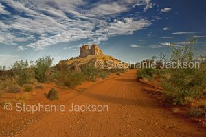 Red road in outback Australia with Castle Rock, geological formation, rising into blue sky, in the Northern Territory.