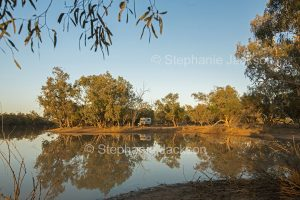 Campervan and woodlands beside and reflected in tranquil waters of Paroo River in Currawinya National Park in outback Queensland Australia