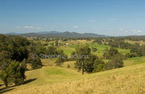 Landscape of rolling hills and distant ranges under blue sky near Dorrigo in northern NSW Australia.