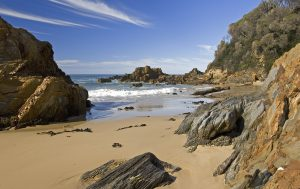Australian coastal landscape with sandy beach, rugged rocks under blue sky at Secret Beach near Mallacoota, Victoria, Australia