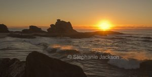 Sunrise over the ocean waves and rocks at Nambucca Heads in NSW Australia.