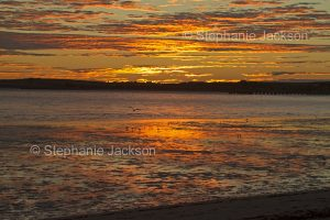 Colourful sky at sunrise reflected in the shallow water beside the beach at Streaky Bay on the Eyre Peninsula in South Australia