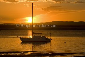 Colourful sunset over the Pacific Ocean and boat at the Town of 1770 in Queensland Australia.