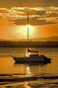 Colourful sunset over the Pacific Ocean and yacht at the Town of 1770 in Queensland Australia.