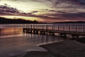Sunset over Australian coastal landscape and jetty at Wingan inlet in Croajingalong National Park, Victoria Australia