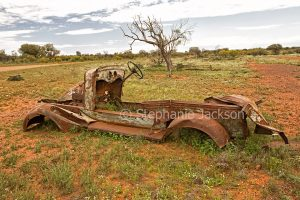 Rusting remains of wrecked car on outback plains near Wanaaring in NSW Australia