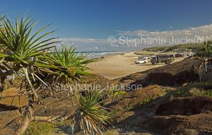 Australian coastal landscape with vehicles parked on vast beach, beside rocks and pandanus palm trees, at Indian Head on world heritage listed Fraser Island in Queensland Australia