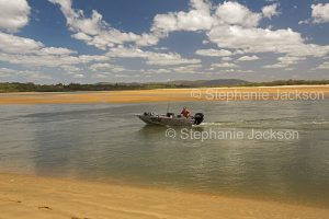 Man in dinghy on calm waters of coastal creek in Eurimbulah National Park, Queensland Australia