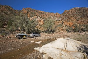 4 X 4 vehicle with camper trailer driving through rocky landscape at Brachina Gorge in the Flinders Ranges National Park in outback South Australia