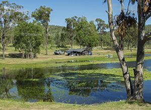 Eungalla dam, west of Mackay in northern Queensland, Australia, with campers on the lake's shaded banks.