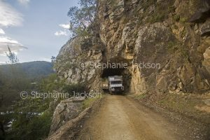 Campervan on road through historic tunnel carved through rock on the old coach road linking the NSW towns of Grafton and Glen Innes.