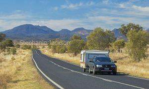 Car and caravan on road through rural landscape near Warrumbungle National Park in NSW Australia.