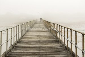 Old wooden jetty disappearing into morning mist at Port Germein on Yorke Peninsula South Australia