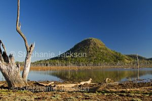 Landscape with conical hill reflected in lake at Nuga Nuga National Park in Queensland Australia