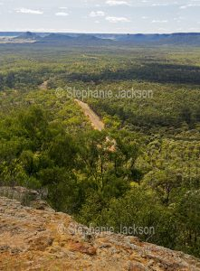 View from high lookout of forested Arcadia Valley, severed by a road, in central Queensland Australia.