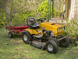 Yellow ride-on mower with red trailer full of soil in a garden in Australia