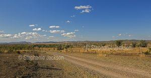 Road slicing through arid rural landscape near Duaringa in central Queensland Australia.