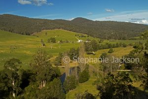 Rural landscape with farmlands surrounded by forested hills near Jindabyne, in the Snowy Mountains region of NSW Australia.