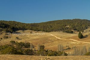 Brown cleared landscape devoid of grass during drought, and hemmed with forested hills near Numeralla in NSW Australia.