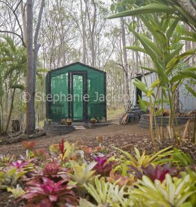 Garden shade house with bromeliads in the foreground.